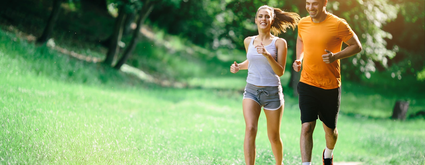 Man and woman jogging in wooded area.